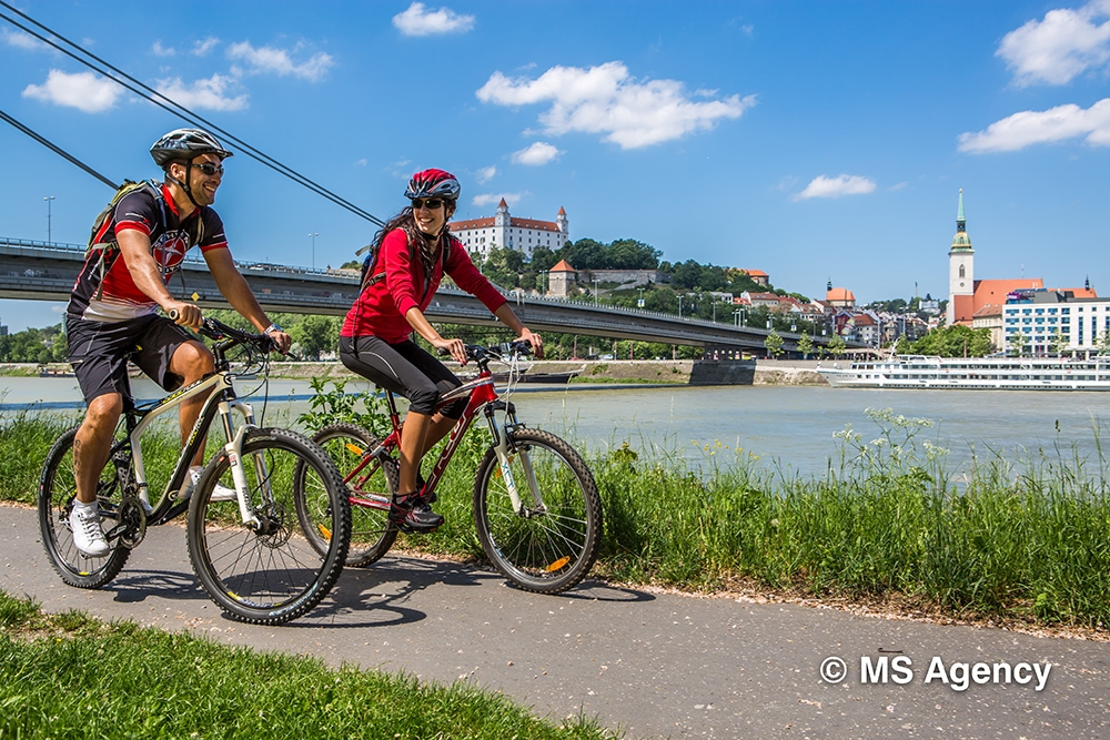 A couple cycling near the Danube riverfront with Bratislava Castle, St