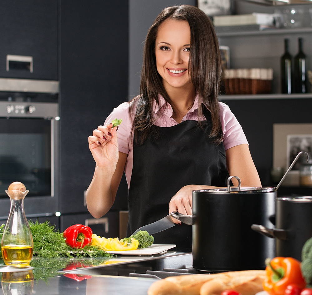 Cheerful young woman in apron on modern kitchen cutting vegetabl