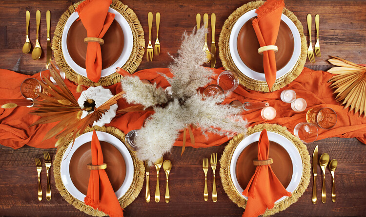 This boho desert collection's sun-bleached plates, woven straw chargers, dried flowers, and wood accents are set off by gleaming gold flatware and textured glasses.