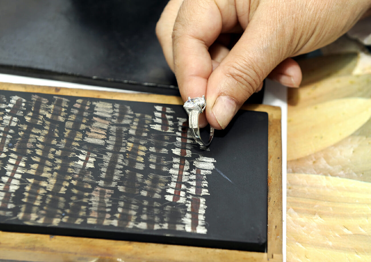 Jeweler inspects silver ring with acid to verify its authenticity