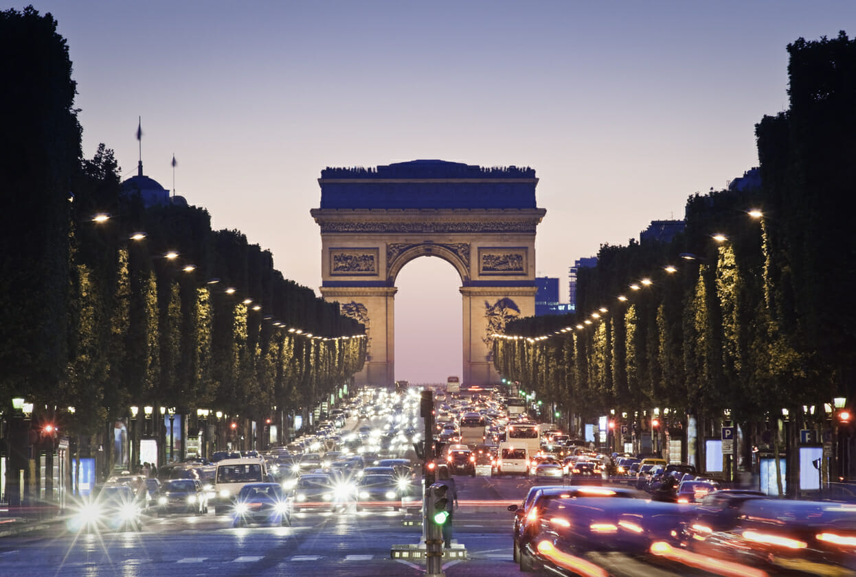 Pretty night time illuminations of the Impressive Arc de Triomphe (1833) along the famous tree lined Avenue des Champs-Elysees in Paris France
