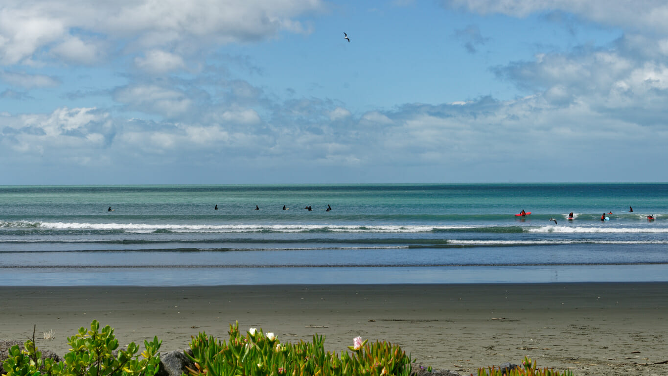 Surfers and swimmers at Sumner Beach, Christchurch, New Zealand.