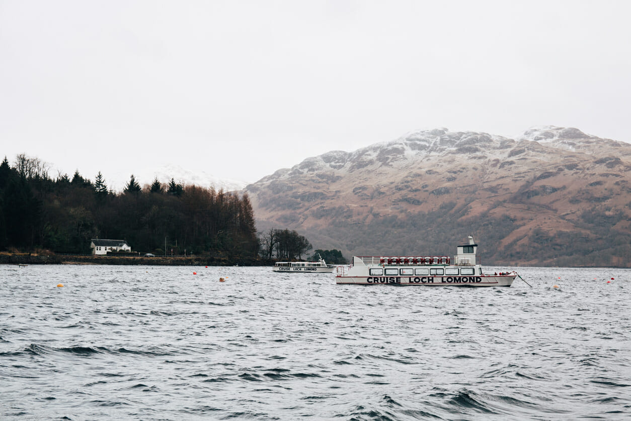 Loch Lomond, Scotland - March 17, 2018: Tour boat on Loch Lomond near Tarbet, Scotland, in spring. The lake is a part of The Trossachs National Park and is the largest inland body of water in UK.