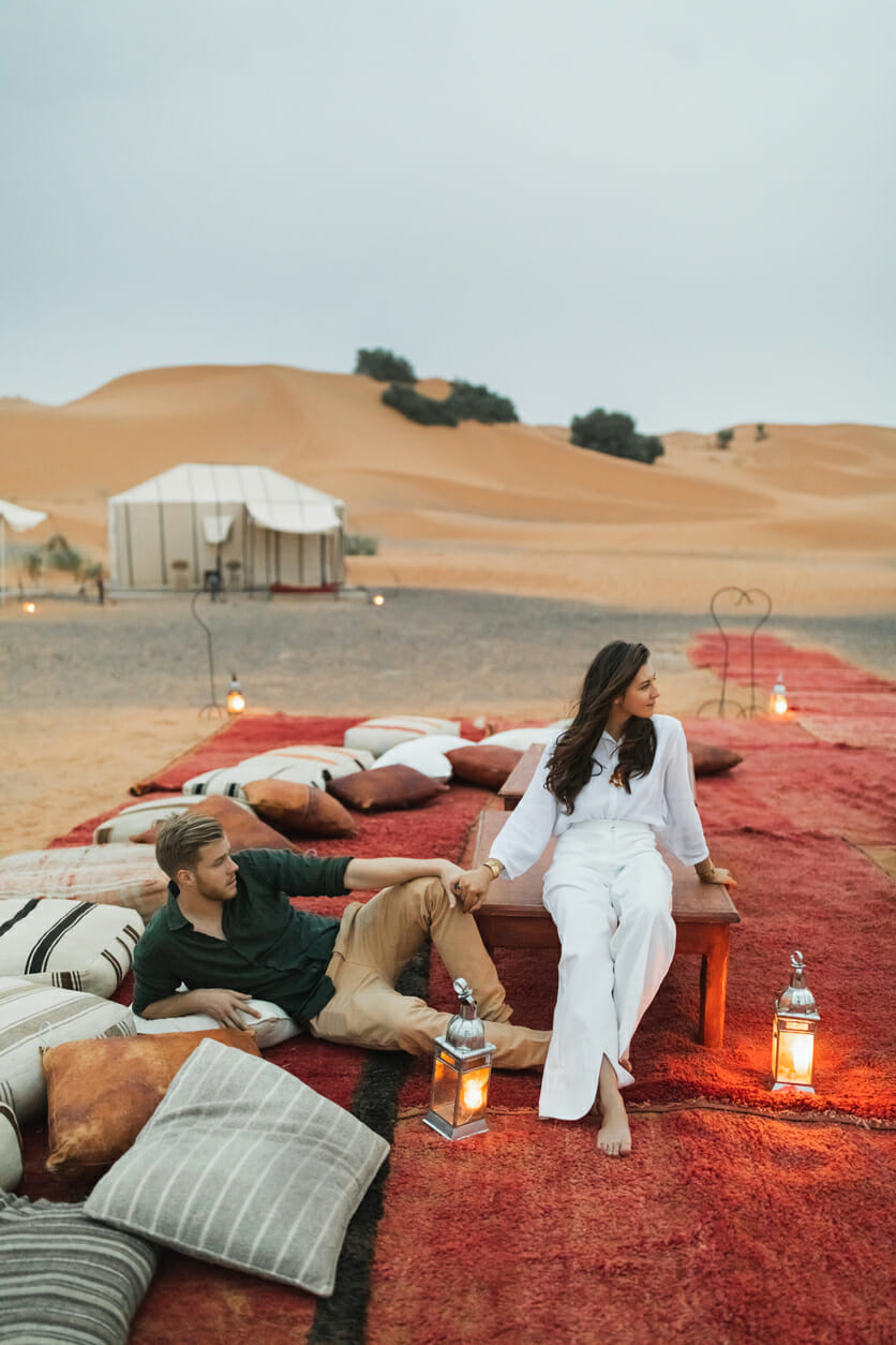 Stylish european couple in love enjoying evening together in luxury glamping camp in Sahara desert, Morocco. Romantic mood, lying on multicolor pillows in Morocco