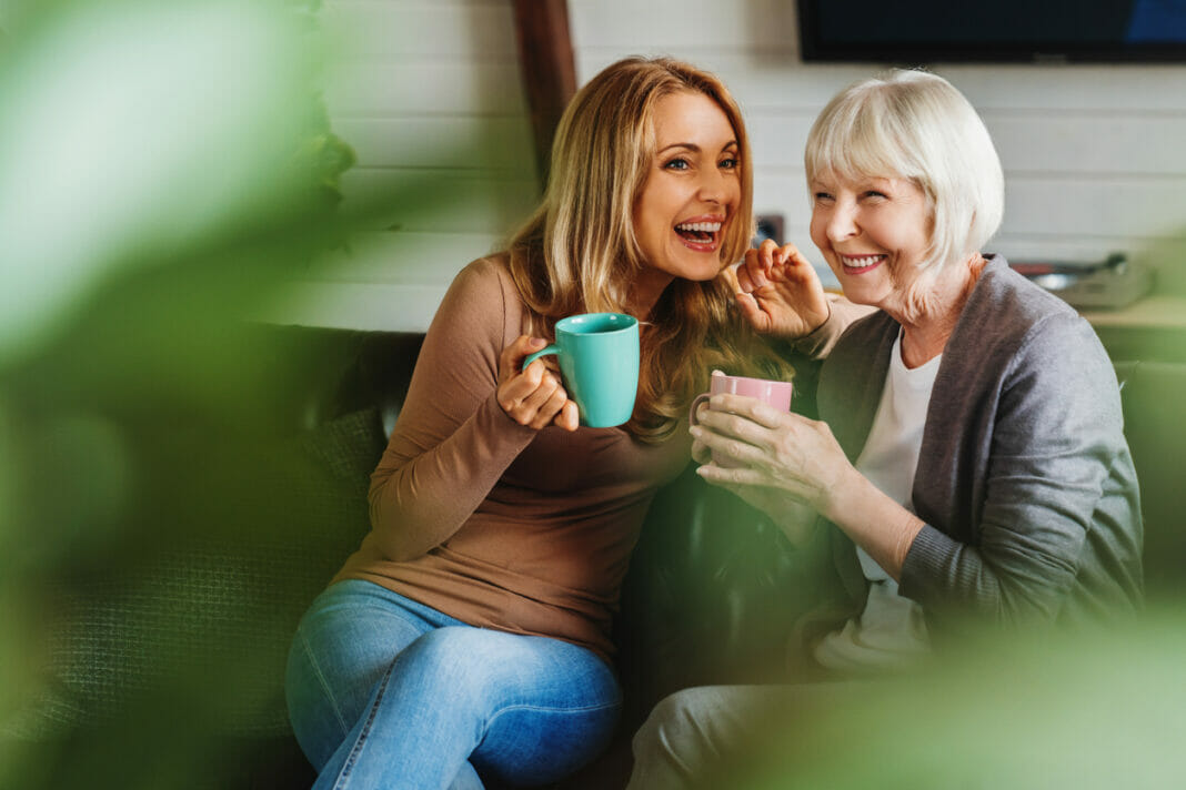 Happy senior mother with adult daughter sitting on couch and holding cups with coffee or tea at home