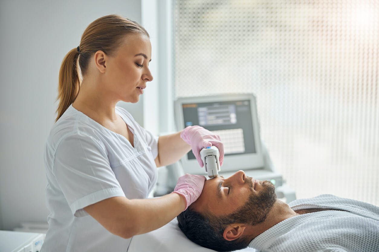 Charming esthetician treating male skin with laser device