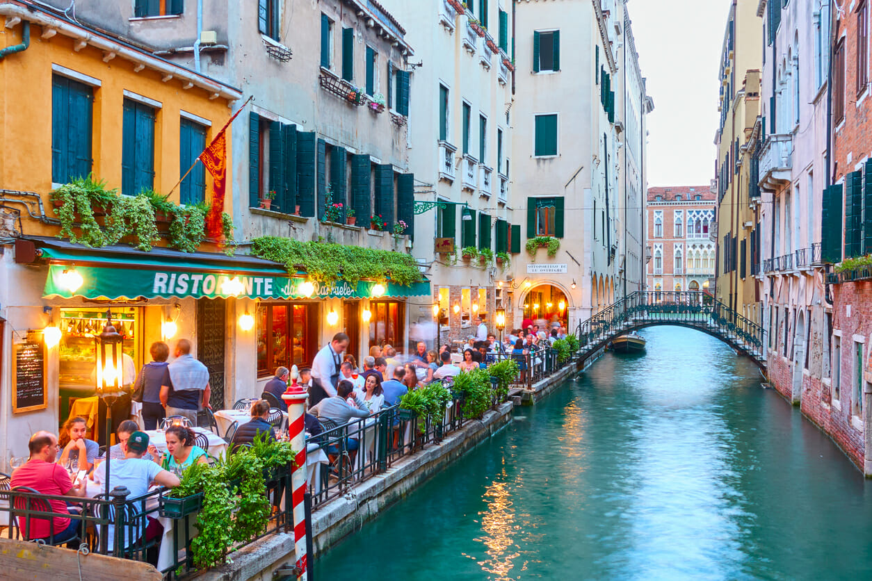 People at restaurant near canal in Venice