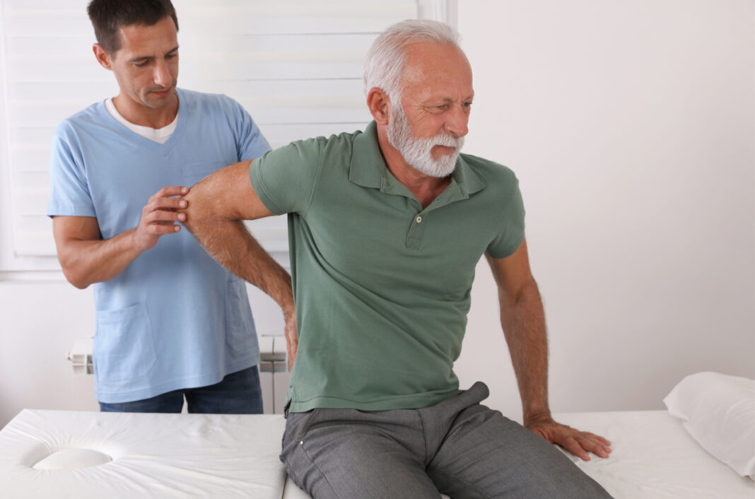Senior man with back pain. Spine physical therapist and paient. Chiropractic pain relief therapy.